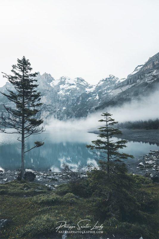 Le brouillard descend sue l'Deux pêcheurs sur une barque au milieu du lac Oeschinensee en Suisse