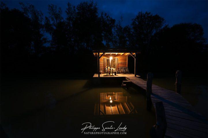 Photo de nuit d'une cabane sur pilotis